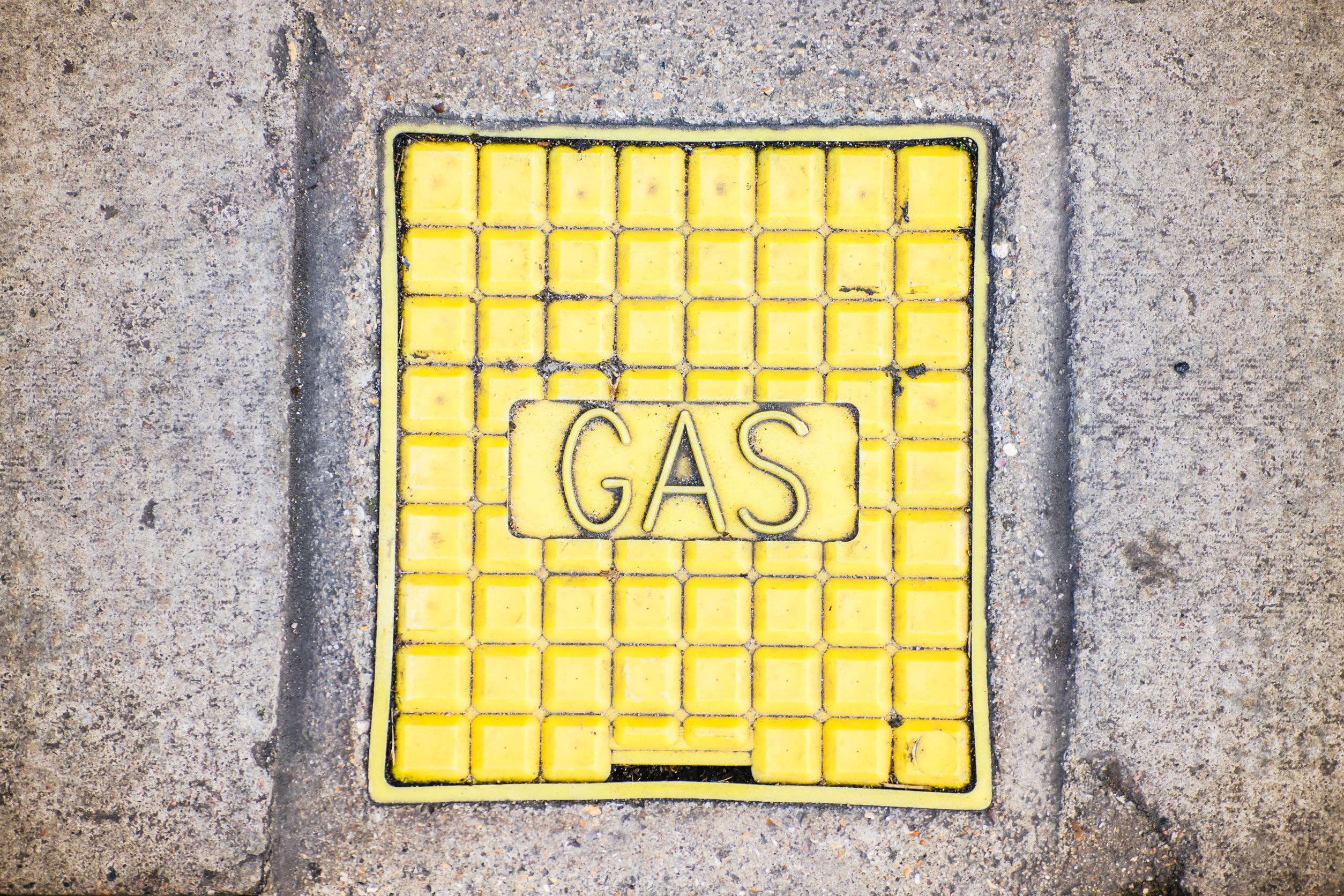 The yellow colored manhole with the gas word from below.